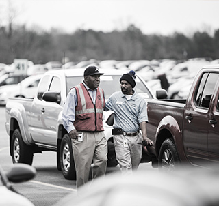 Two employees in a car storage lot