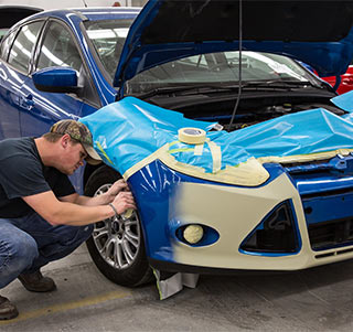 A mechanic working on a car's front