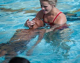 Woman helping child in pool
