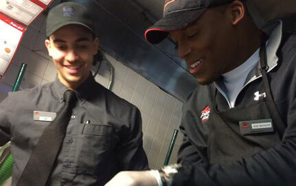Two Pizza Hut workers prep a pizza