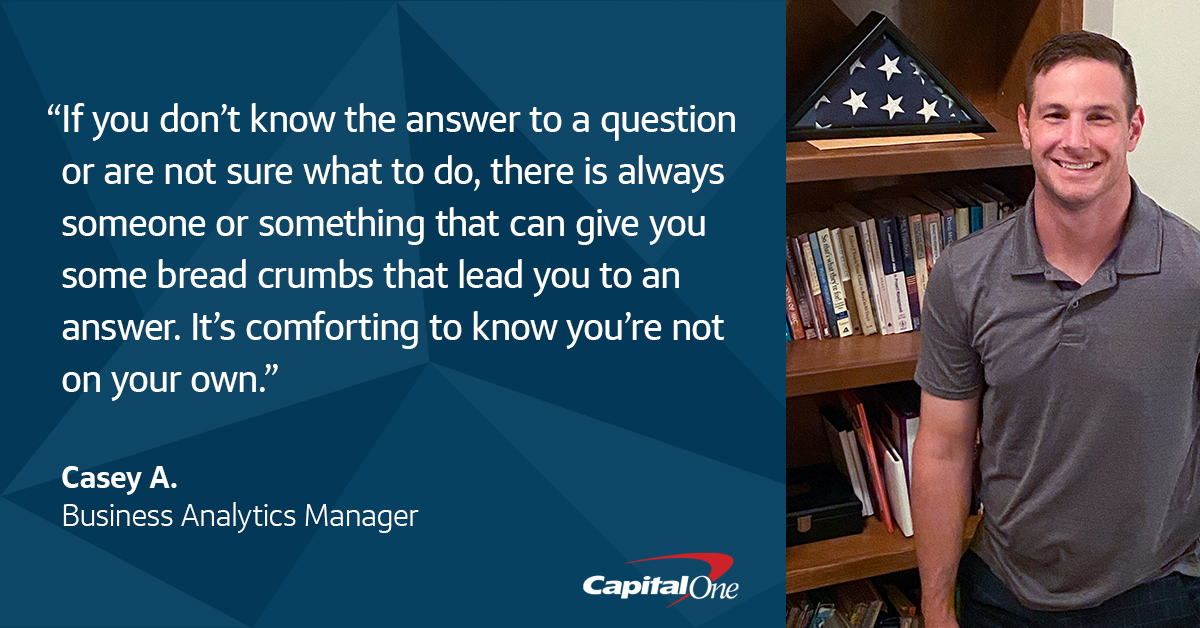 """A quote image with picture of Capital One veteran associate Casey A. standing in front of a bookshelf with his folded military flag, that says, """"If you don't know the answer to a question or are not sure what to do, there is always someone or something that can give you some bread crumbs that lead you to an answer. It's comforting to know you're not on your own."""" – Casey A., Capital One Business Analytics Manager"""