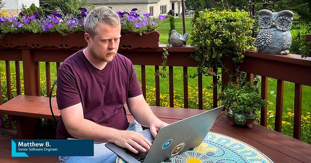 Capital One associate sits on his back porch working on his laptop outside