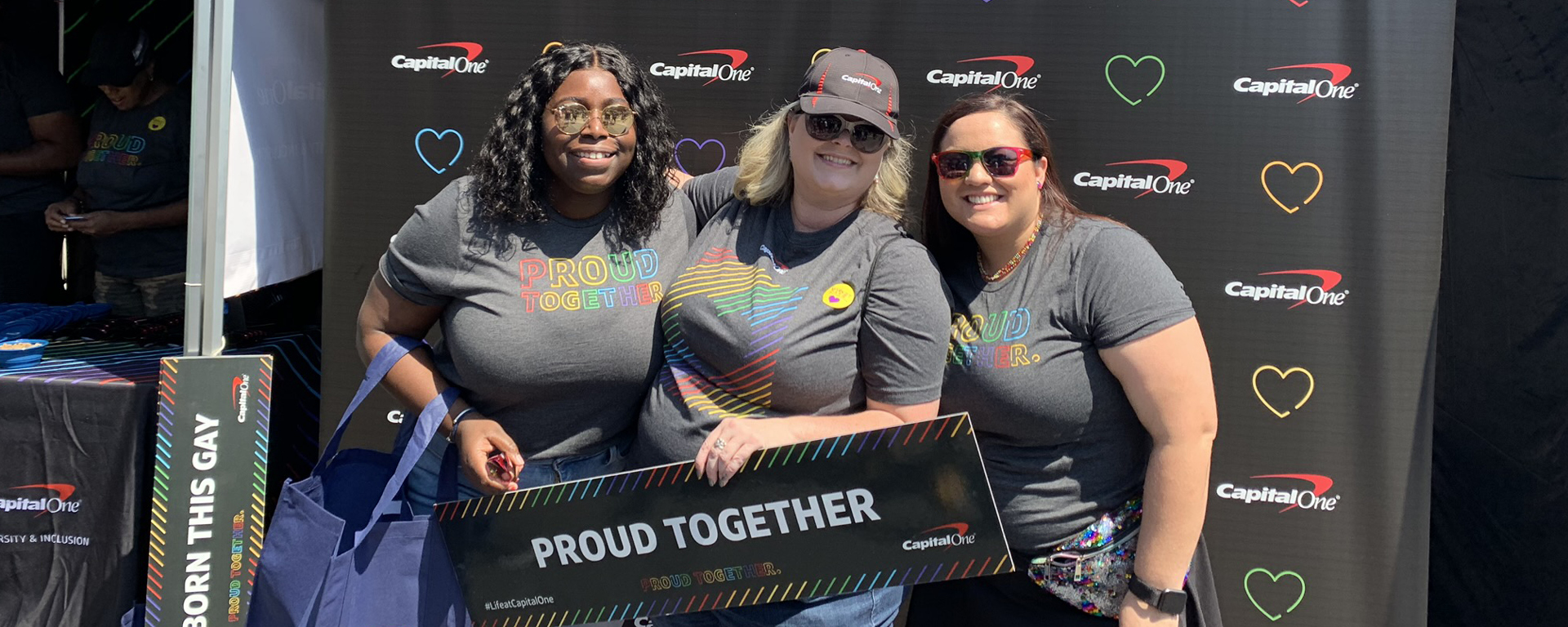 Three Capital One associates stand in front of a black backdrop with colorful hearts holding a sign that says