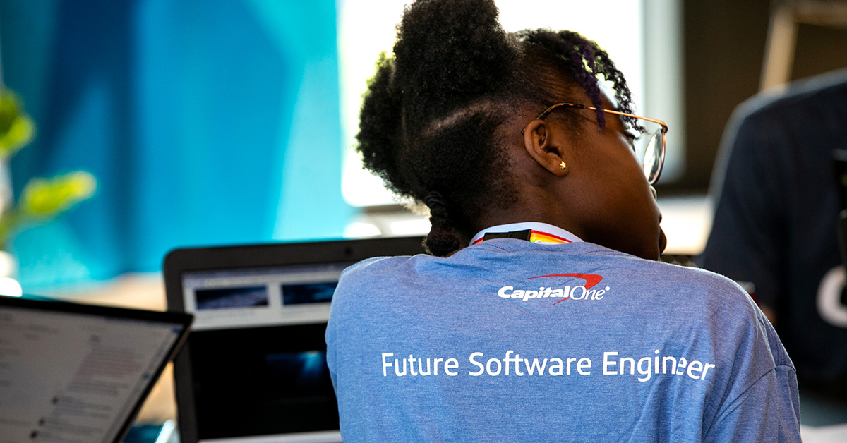 Woman with Future Software Engineer at Capital One shirt sits with her back facing, representing how Blacks in Tech at Capital One creates an inclusive community of technologists to help associates grow and thrive