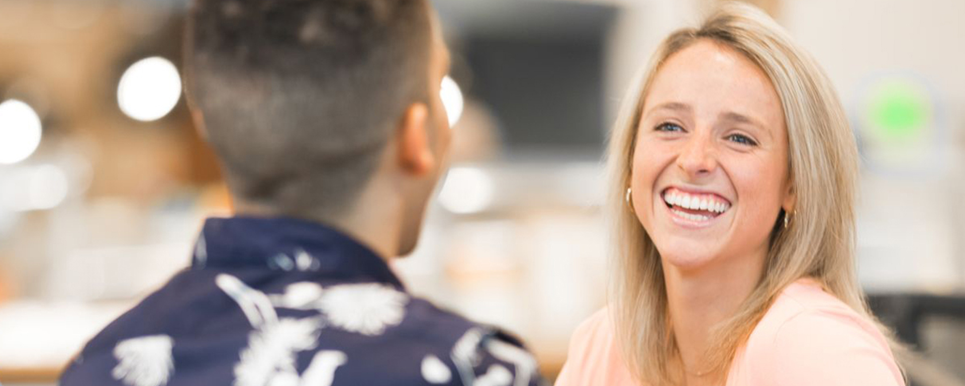 Capital One associate smiles and laughs with her colleague whose back is towards the camera, talking about Capital One's Battle of the Binge-Watching, a bracket for tv shows used to help the community