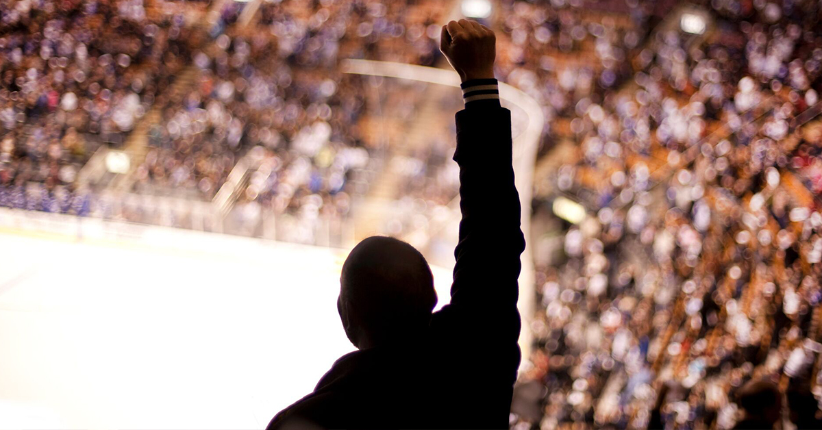 Silhouette of a man standing in a full arena with his fist in the air Capital One