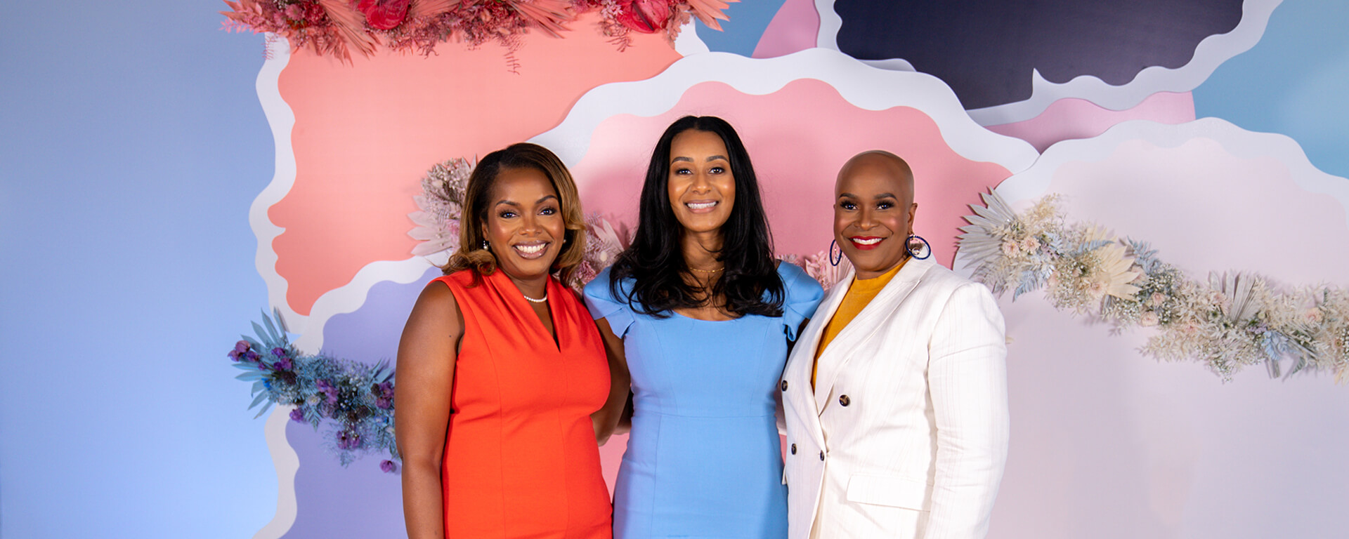 Three Black Capital One female leaders stand in front of a pink and blue backdrop at the Black Girl Magic Digital Summit