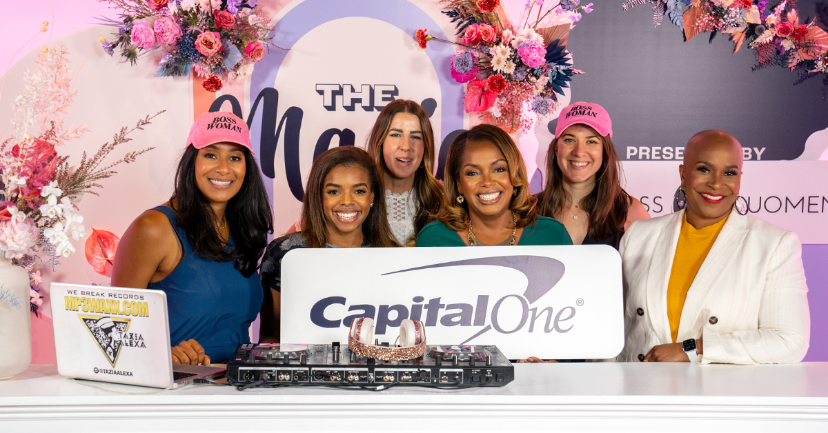 A group of Capital One associates stand in front of a blue and pink backdrop at the Black Girl Magic Digital Summit, holding a Capital One sign