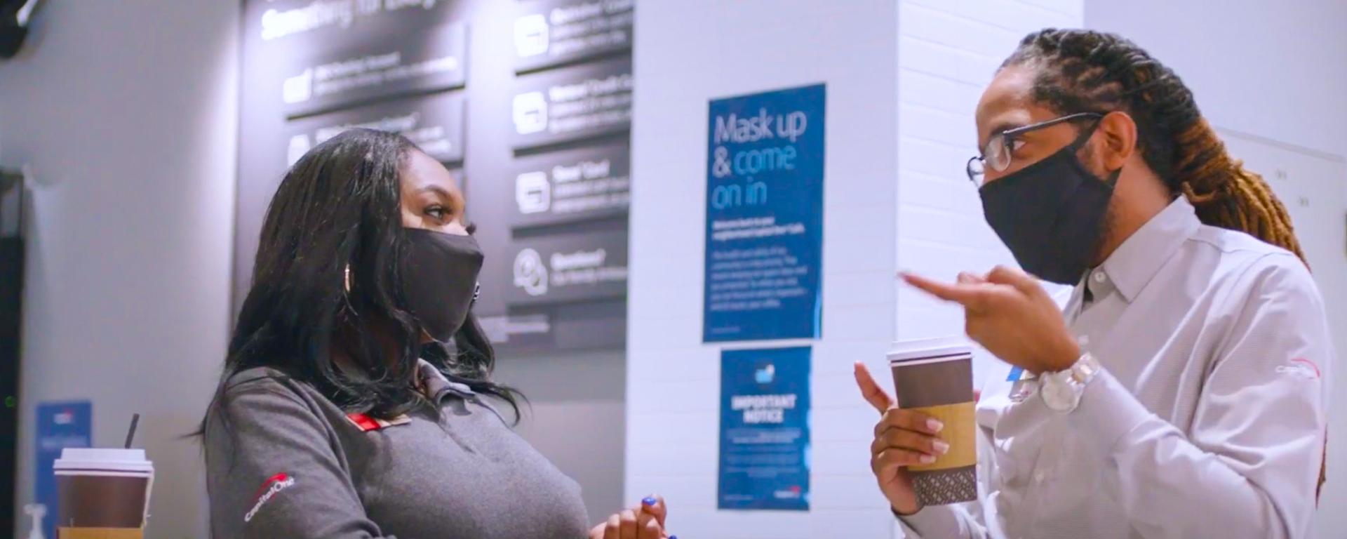 Capital One cafe associate talks to a customer wearing masks