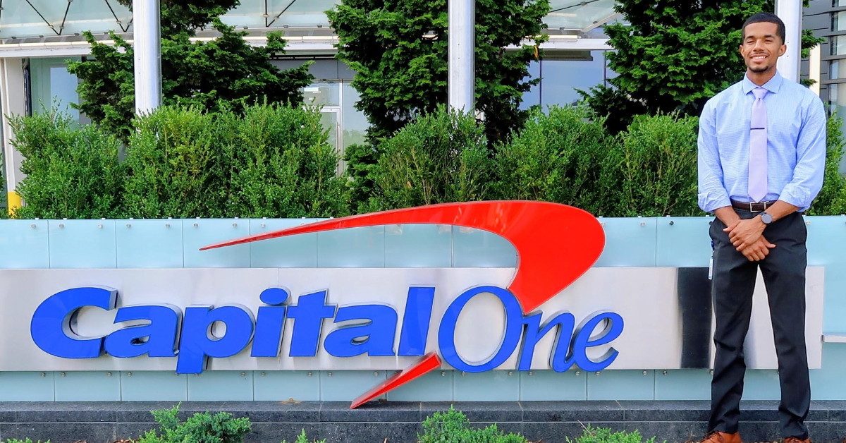 Carlton, a Capital One Tech associate, stands in front of the Capital One sign outside