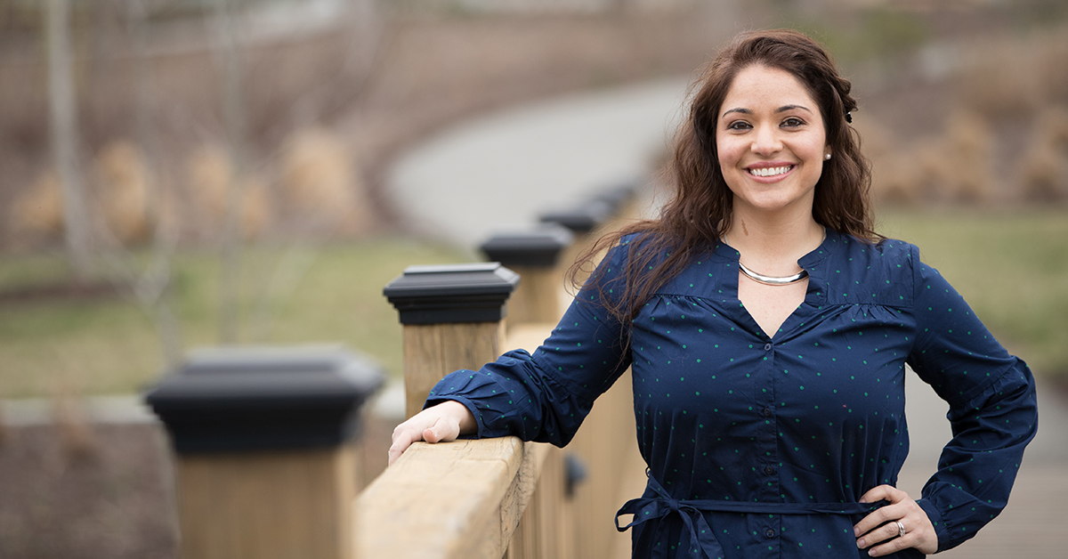 Woman stands and smiles outside leaning against railing at Capital One campus