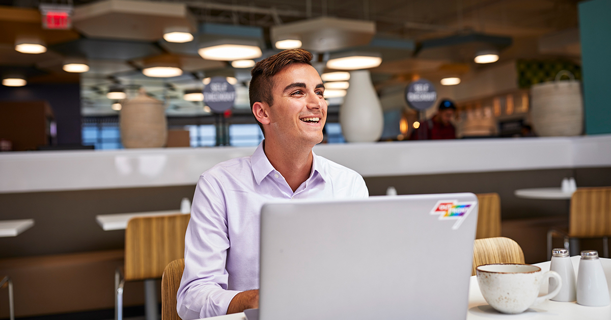 Capital One student and grad associate sits at his laptop on campus