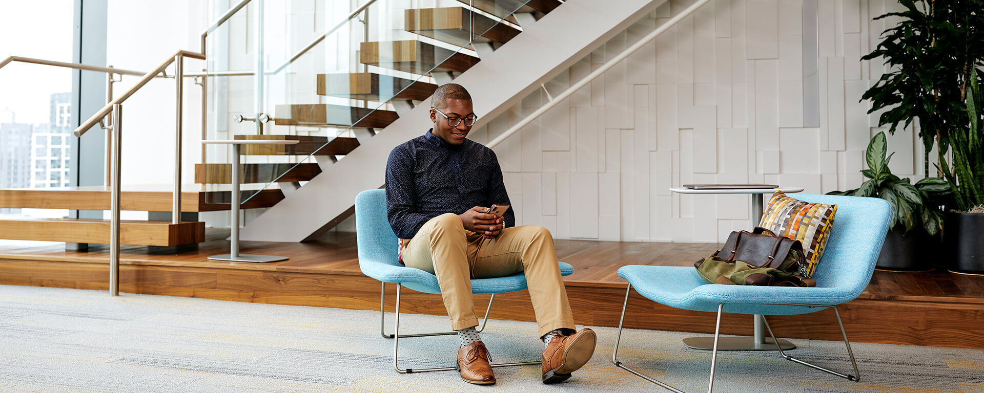 Capital One student and grad associate sits in a chair in front of a stairwell at a Capital One office and talks about his internship experience