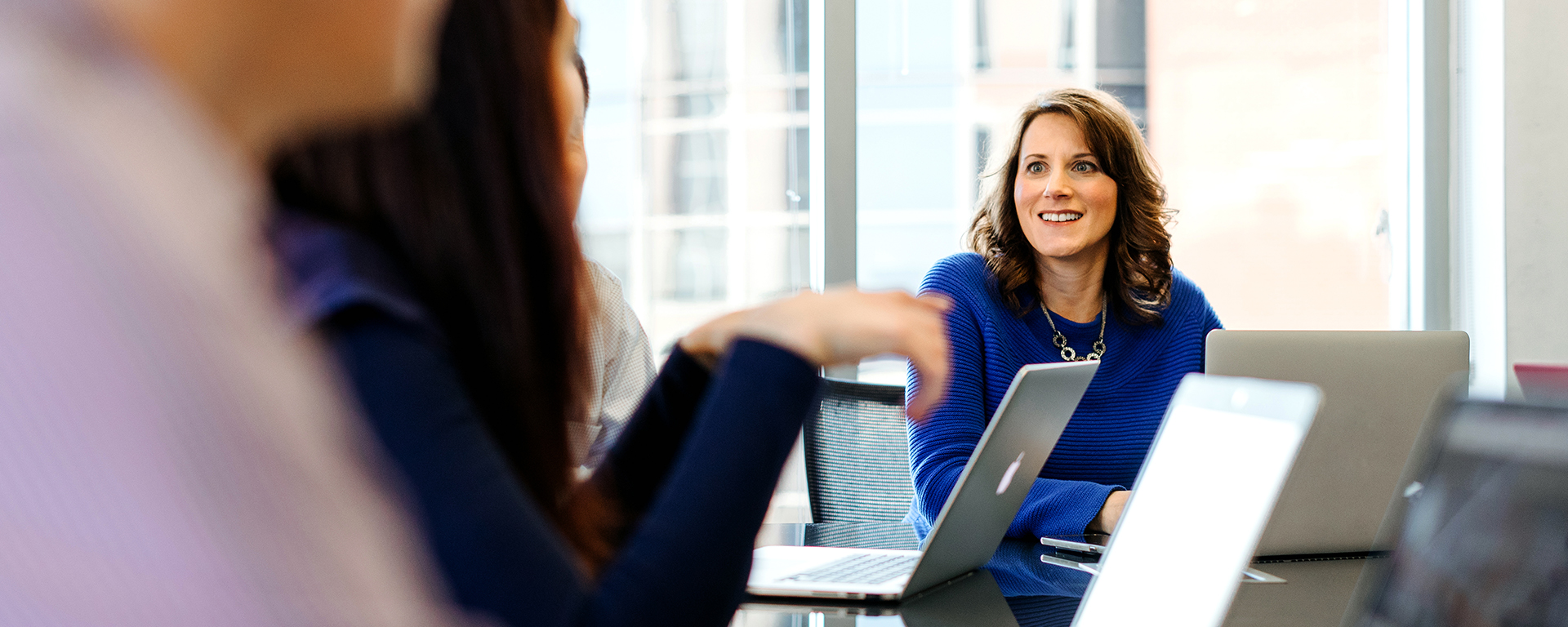 Woman sits at table and talks to her Software Engineering team at Capital One