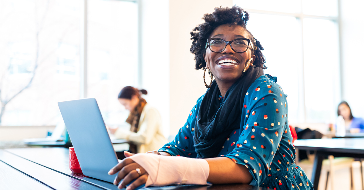 Capital One Tech associate sits at her laptop and laughs