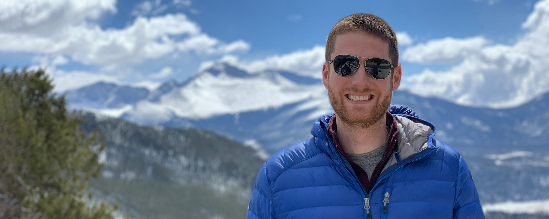 Jared, a Capital One tech associate, stands in front of snowy mountaintops