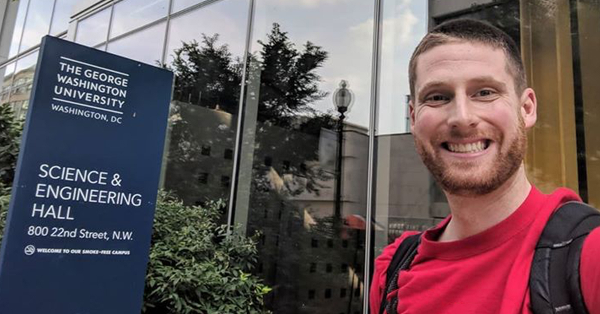 Jared, Capital One tech associate, stands in front of the Science & Engineering Hall sign at at George Washington University (GW) where he received his Masters in Computer Science