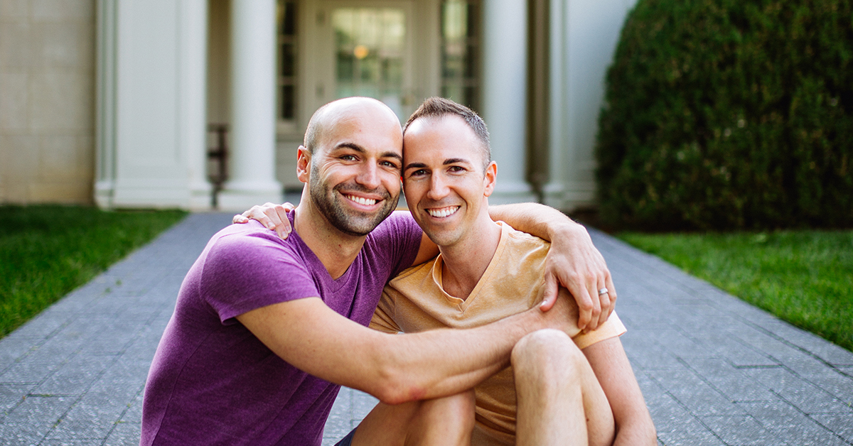 MC, Capital One Director, and his partner sit on a stone pathway in front of a building as he talks about immigrating to the US before same sex marriage was legal