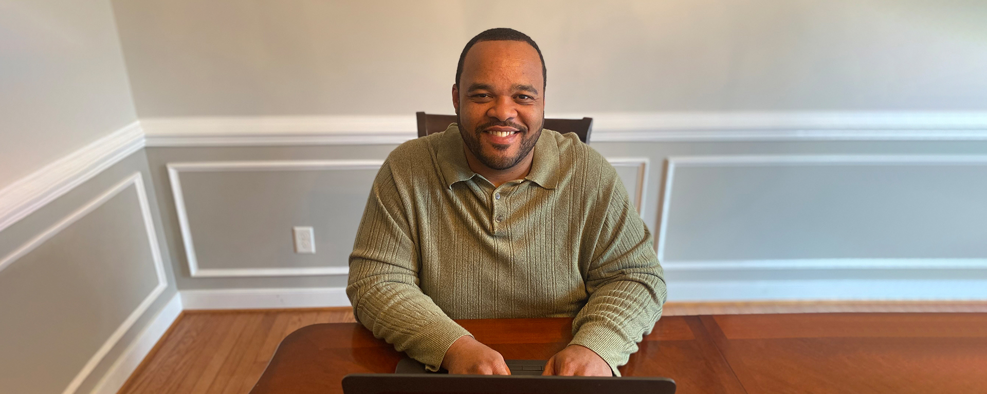 Tyrell, a Capital One associate, sits at his desk working from home and talks about Capital One having his dream job