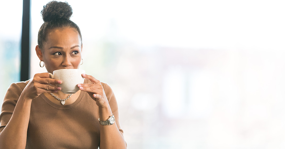 Woman sitting in Capital One sips on her coffee