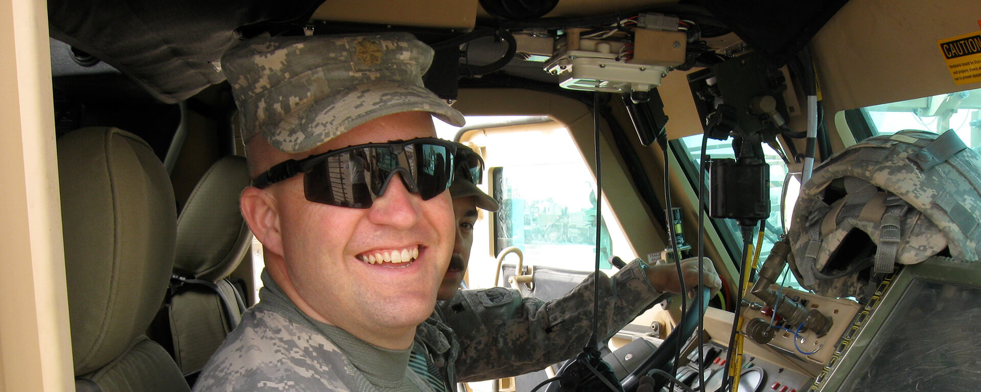 Chris, a Tech leader at Capital One, sits in a military vehicle in his digis while deployed in Afghanistan