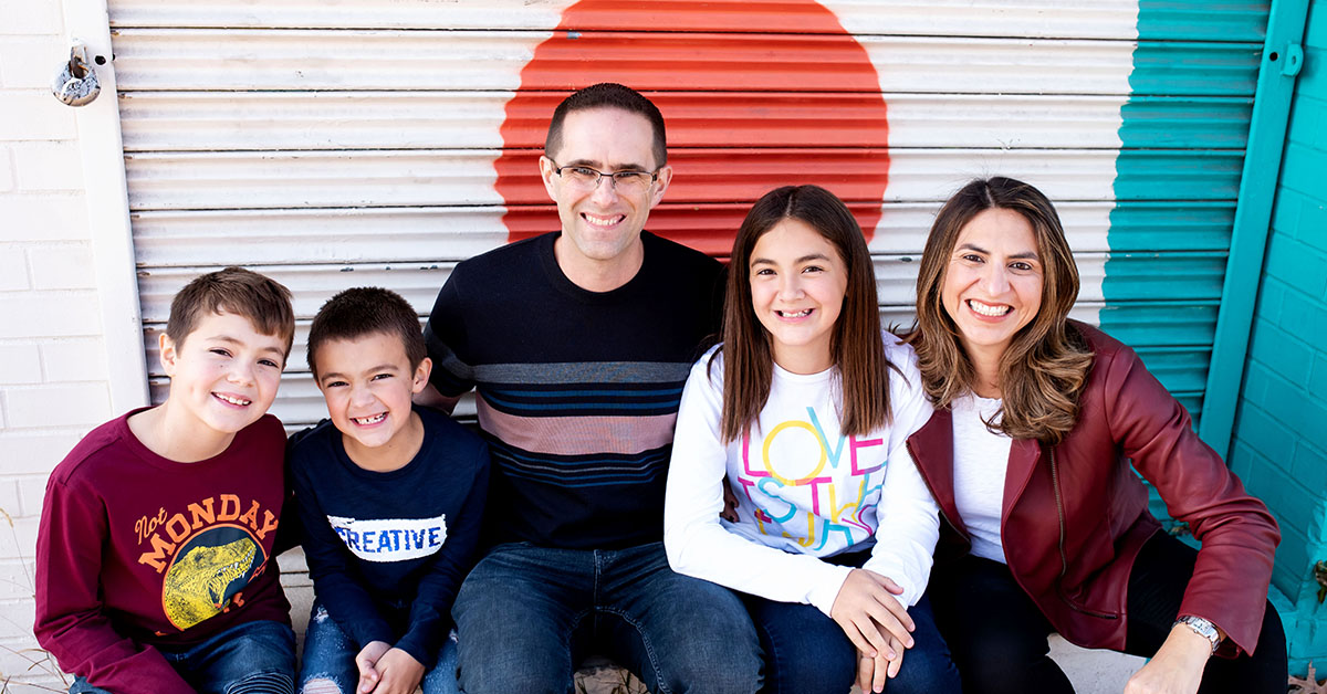 Cinthia Lopez, Capital One VP of Students and Grads Recruiting and Programs, sits in front of a storage unit door with her husband and 3 children, and talks about her experiences as an immigrant and in leadership