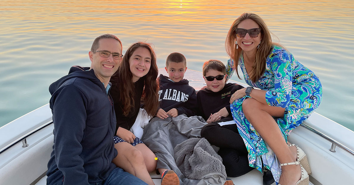 Cinthia Lopez, Capital One VP of Students and Grads Recruiting and Programs, sits in a boat on the water at sunset with her family
