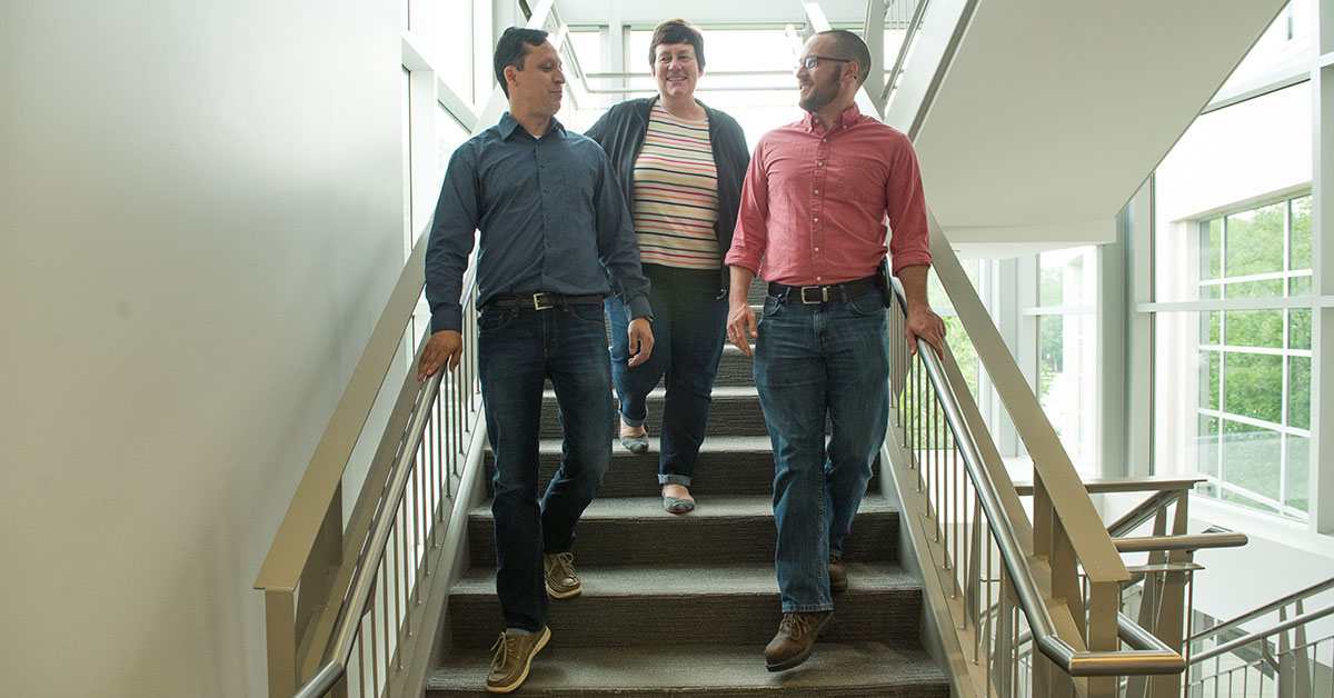 woman discussing diversity of thought on stairs with two men
