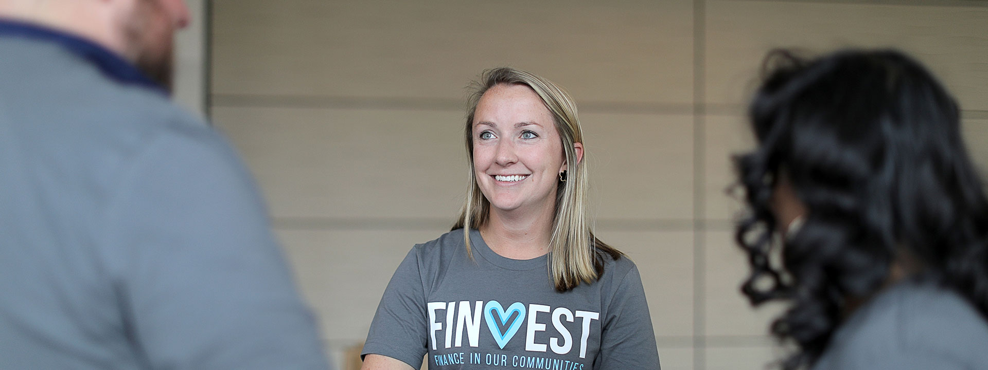 Shannon talking to colleagues while wearing a FINVEST shirt