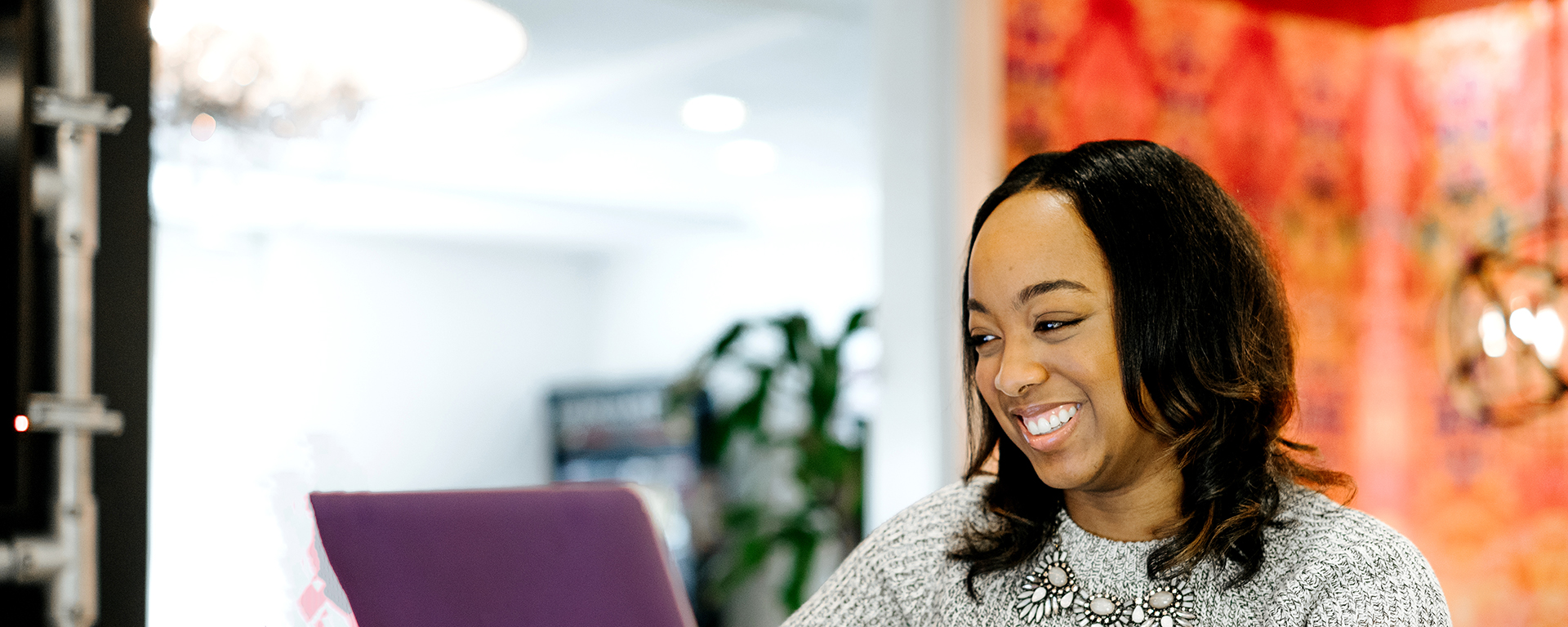Woman on laptop staying positive while looking for a job at Capital One