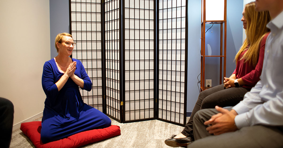woman leading a meditation session at work