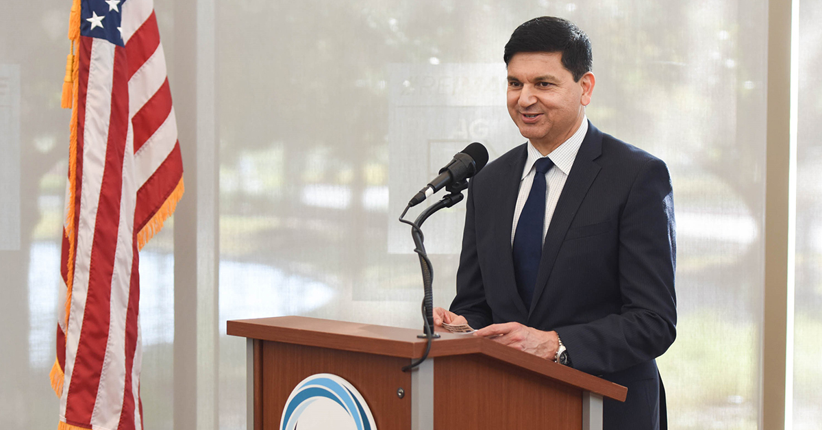 Sanjib Yajnik, president of Capital One's Financial Services, stands at a podium and gives a speech about the lessons he's learned in leadership