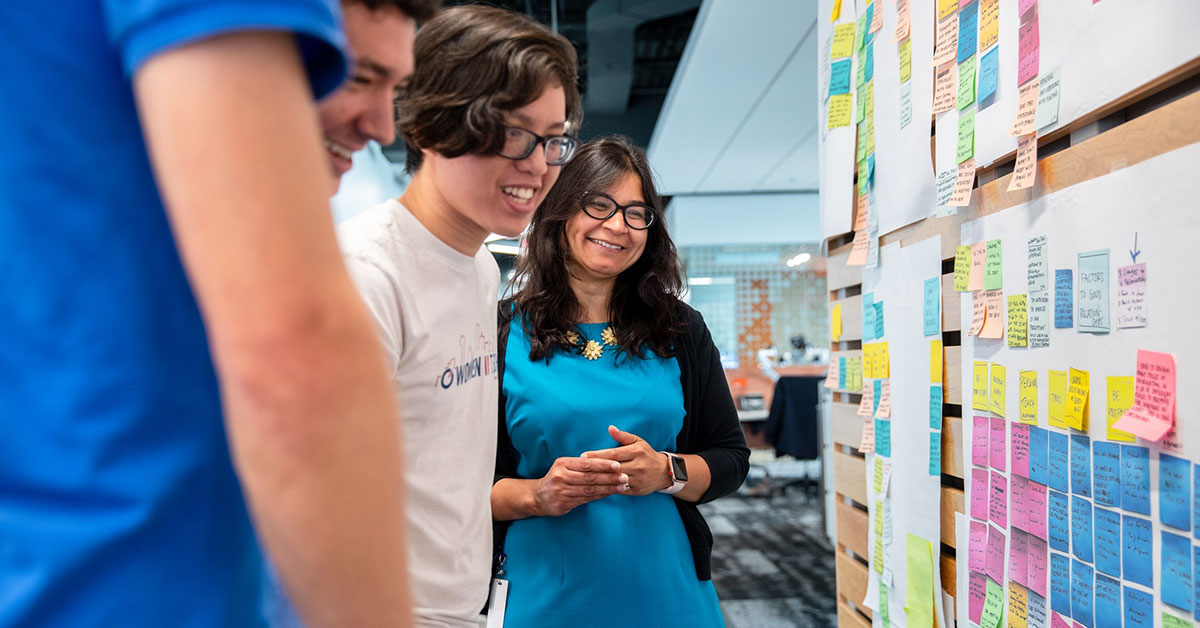 woman working with young men at design thinking board