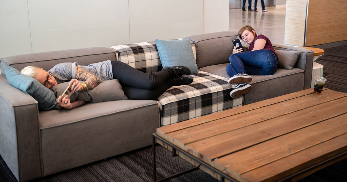 women relaxing on a couch at work