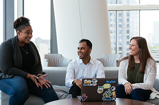 Three employees talking together in an open common area.