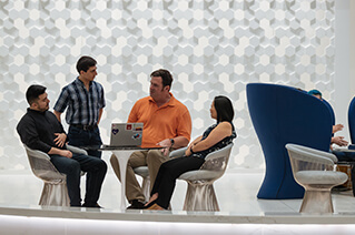 Four employees talking in an open common area.