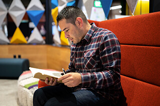 Employee reading a book in an open common area.