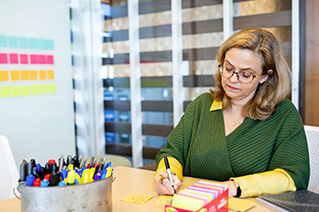Employee making notes at a table using different colored markers.