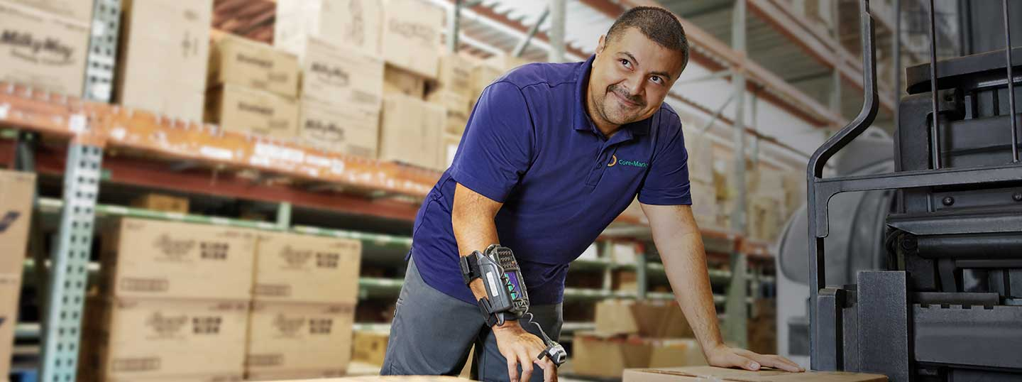 Smiling man in warehouse leaning on boxes
