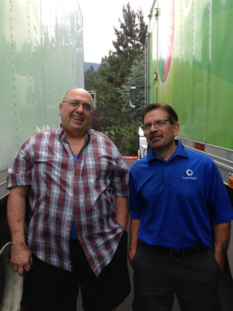 richard standing between two trucks with a coworker