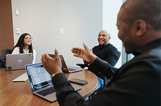 Three employees smiling and talking in a conference room.