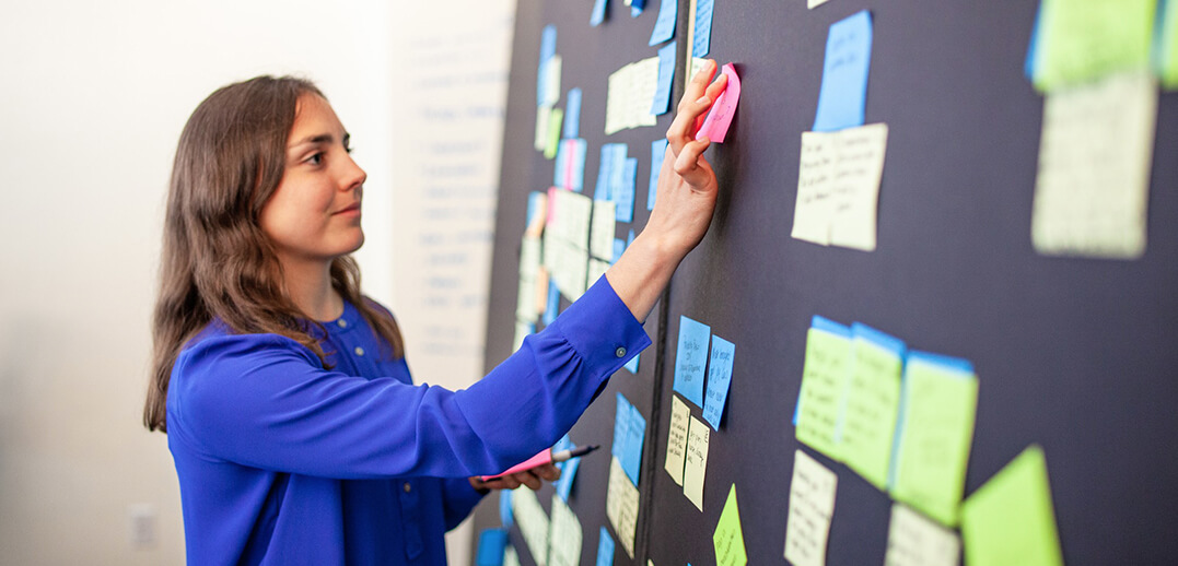 Woman placing sticky notes on a panel.