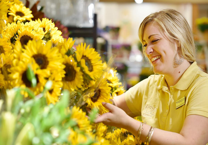 Employee smiling while looking at a large arrangement of yellow flowers