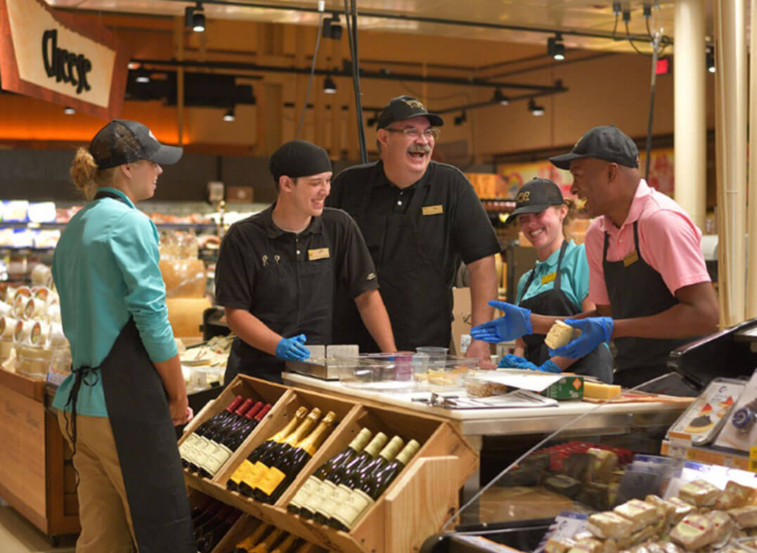 Employees around a wine and cheese counter