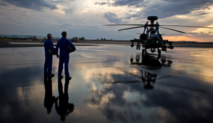 Two service members standing next an Apache helicopter