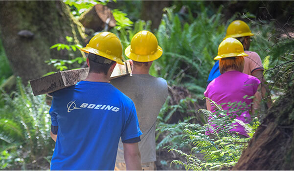 Men and women wearing hard-hats and walking in wooded area