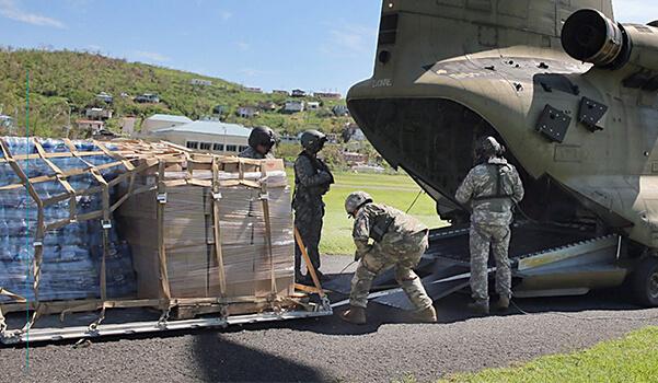 military loading cargo onto plane