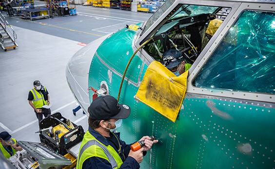 People working on a bare metal airplane fuselage