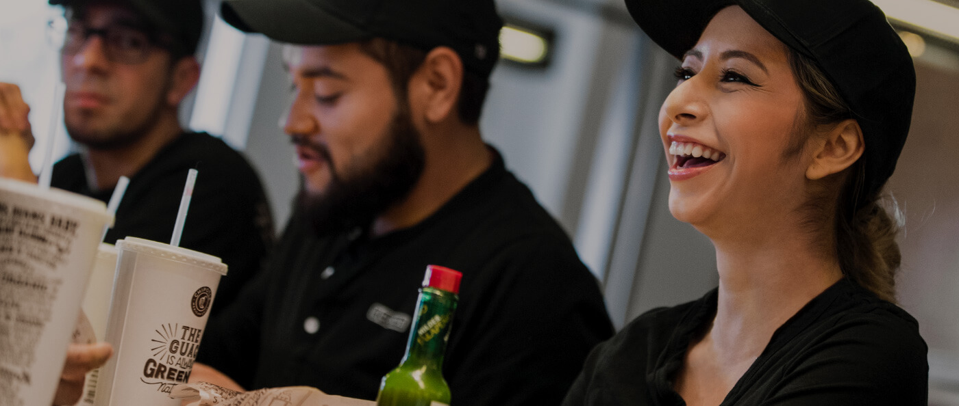 Chipotle Restaurant Crew team members laugh and enjoy a family-style meal together in the restaurant.