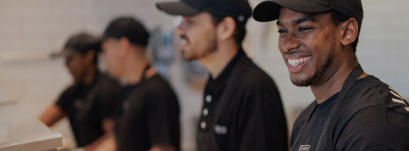 Crew members working happily together to serve bowls and burritos to restaurant guests.